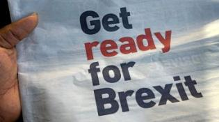 Hand holding newspaper that reads GET READY FOR BREXIT